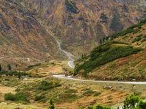 Hohe alpine Straße in der Marsmensch ähnlichen Landschaft mit BMW-Auto Lizenzfreies Stockbild