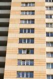 Hohe Aufstiegsgebäudefassade, acht Böden, dunkle gelbe Wand und Glasfenster Lizenzfreie Stockfotos