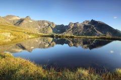 Hohe Berge reflektierten sich in einem Glazial- See, Norwegen stockfotos