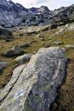Hohe Bergscape mit Fluss-Steinen und Schnee lizenzfreie stockfotos