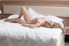 Hohe Frau der Schönheit legen in reizvolle Wäsche auf Bett Stockbild
