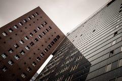 Hohe Gebäude, das erste ist rot und Ziegelstein, zweite ist Glas Stockfotografie