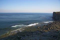 Hohe Klippe über dem Meer, die Klippe steigt in das Meer, in viele spritzenden Wellen und in Steine ab Stockfotos