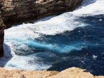 Hohe Klippe auf dem Meer mit Wellen Lizenzfreie Stockbilder