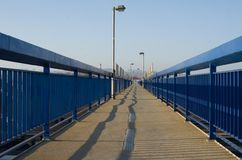 Hohe Lampen zeichneten durch blaues Geländer und Himmel im Hintergrund lizenzfreies stockbild