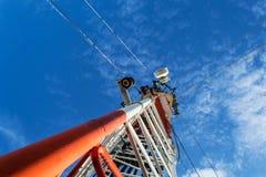 Hohe Mastmetallbautelekommunikation auf Turm mit blauem s stockfotografie