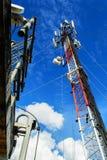 Hohe Mastmetallbautelekommunikation auf Turm mit blauem s Lizenzfreie Stockfotos