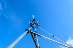 Hohe Mastmetallbautelekommunikation auf Turm mit blauem s Lizenzfreies Stockbild
