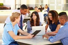 Hohe Schüler, die auf dem Campus mit Lehrer arbeiten Lizenzfreie Stockfotos