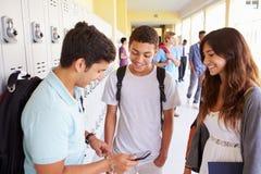 Hohe Schüler durch die Schließfächer, die Handy betrachten Lizenzfreies Stockfoto