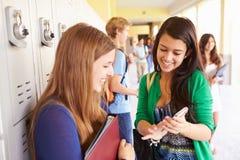 Hohe Schüler durch die Schließfächer, die Handy betrachten Stockfotos