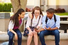 Hohe Schüler, die Handy auf Schulcampus verwenden Lizenzfreies Stockbild