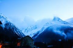 Hohe Schnee-mit einer Kappe bedeckte Berge im Nebel lizenzfreie stockbilder