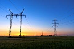 Hohe Stromleitungen an der Dämmerung Lizenzfreies Stockbild