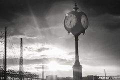 Hohe Uhr gegen einen Sonnendurchbruch-Himmel Stockbild