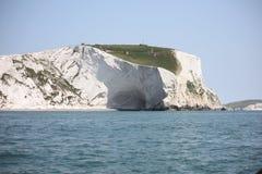 Hohe weiße Klippen, die über ein blaues Meer hochragen Stockbild