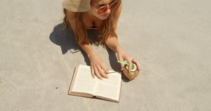 Hohe Winkelsicht der kaukasischen Frau im Hut ein Buch auf dem Strand 4k lesend stock video footage