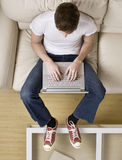 Hohe Winkelsicht des kühlen jungen Mannes, der auf Laptop schreibt Lizenzfreie Stockbilder