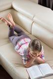 Hohe Winkelsicht des Mädchenlesebuches beim auf Sofa zu Hause liegen Lizenzfreie Stockbilder