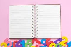 Hohe Winkelsicht des Notizbuches und mehrfarbige hölzerne Zahlen auf minimalistic Konzept des rosafarbenen Hintergrundes Lizenzfreie Stockbilder