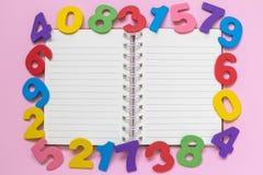 Hohe Winkelsicht des Notizbuches und mehrfarbige hölzerne Zahlen auf minimalistic Konzept des rosafarbenen Hintergrundes Lizenzfreies Stockfoto