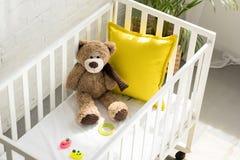 hohe Winkelsicht des Teddybären, anderer Spielwaren und des gelben Kissens in der Babykrippe lizenzfreie stockfotografie