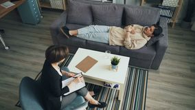 Hohe Winkelsicht des Teenagers sprechend mit dem Psychologen, der auf Couch im B?ro liegt stock footage