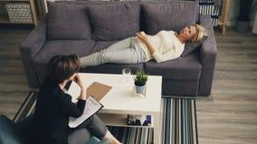 Hohe Winkelsicht von Dame Probleme mit dem Therapeuten teilend, der auf Couch im B?ro liegt stock video footage