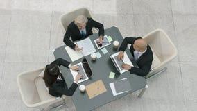 Hohe Winkelsicht von drei Unternehmensgeschäftsleuten, die im Büro sich treffen stock footage