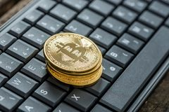 Hohe Winkelsicht von vier goldenen bitcoins auf einer Tastatur Stockbilder