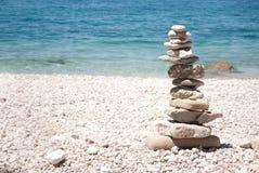 Hohe Zenpagode auf weißem Strand mit Meer im Hintergrund Lizenzfreie Stockfotografie