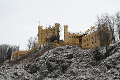 Hohenschwangau Castle. In Bavaria, Germany on a snowy day with a view of the towers, walls, façade a rock outcrop on a hill and some trees stock photography