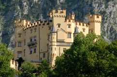 Hohenschwangau Castle in Bavaria between trees and rocks (Germany) Royalty Free Stock Photo