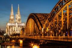 Hohenzollern bro och Cologne domkyrka på skymning Arkivfoton