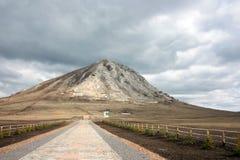 Hoher Berg auf einem Hintergrund des grauen Himmels Stockfotos