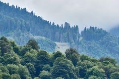 Hoher Berg mit den grünen Steigungen versteckt in den Wolken und im Nebel stockbild