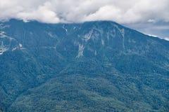 Hoher Berg mit den grünen Steigungen versteckt in den Wolken und im Nebel stockfotografie