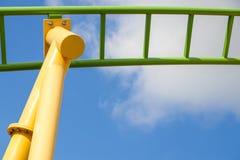 Hoher Blick des gelben und grünen Achterbahnabschlusses mit blauem Hintergrund des bewölkten Himmels Stockbilder