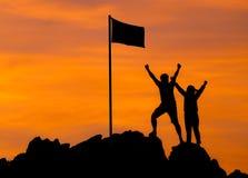 Hoher Erfolg, das Schattenbild mit zwei Leuten stellen hohe Hand her stockbilder