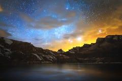 Hoher Gebirgs-See im Nord-Kaukasus, umgeben durch epische Felsen und einen sternenklaren Himmel des hellen Winters bei Sonnenunte Stockfoto
