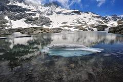 Hoher Gebirgslandschaft mit See und Schnee Stockfotografie