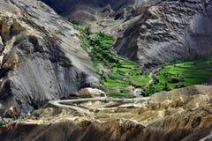 Hoher Gebirgstibetanisches Dorf: unter den grauen und gelben Felsen sind Terrassen grüne Felder, graue Bandkurvenreiche straße, L Stockbild