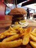 Hoher Hamburger mit den Kartoffeln gedient am Restaurant stockbilder