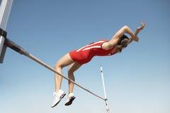 Hoher Jumper In Midair Over Bar Stockfotos