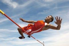 Hoher Jumper In Midair Over Bar Stockbild