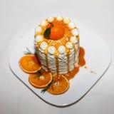 Hoher Kuchen mit Orangen und Karamell auf einer weißen Platte Stockbild