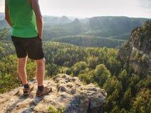 Hoher Läufer im grünen Unterhemd und in den schwarzen Hosen Furchtloser Junge am Rand lizenzfreies stockfoto