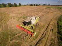 Hoher moderner Mähdrescher der Winkelsicht am Ernten des Weizens Stockfotografie