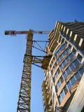 Hoher orange Kran, der ein neues Geschäftsgebäude konstruiert lizenzfreies stockbild