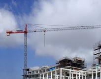 Hoher roter Kran auf einer Großbaustelle mit blauem Himmel und Wolken des Metallrahmenbaugerüsts Lizenzfreies Stockfoto